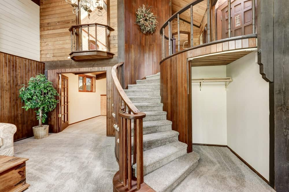This is a beautiful Rustic-style foyer with gray carpeted floors that also extend to the steps of the wooden staircase with wooden railings that leads to the second floor. the small nook by the stairs has a floating shelf and hooks for the coats and hats.