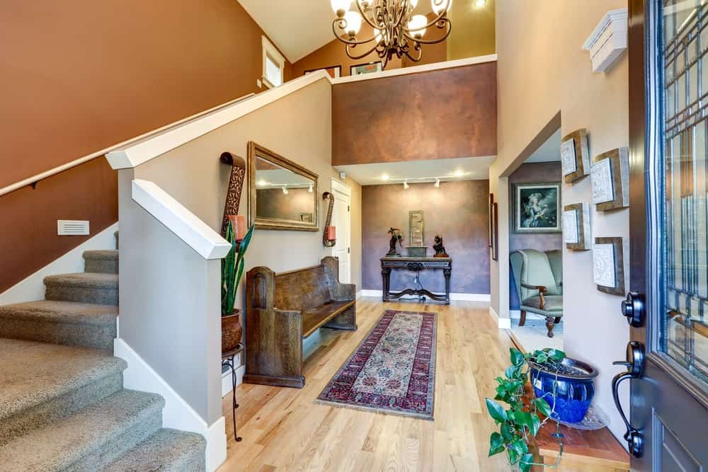 The high ceiling of this warm Rustic-style foyer is adorned with a majestic wrought iron chandelier that gives off warm yellow lights. This complements the light hardwood flooring that has a purple patterned area rug in front of a wooden bench.