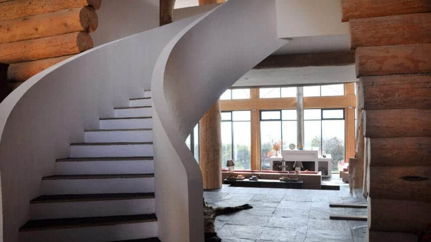 Upon entry of this Rustic-style foyer, you are welcomed by the gorgeous white winding staircase with wooden steps that lead to the second floor. The large living room hall that is filled with tall glass walls is also visible from the foyer.