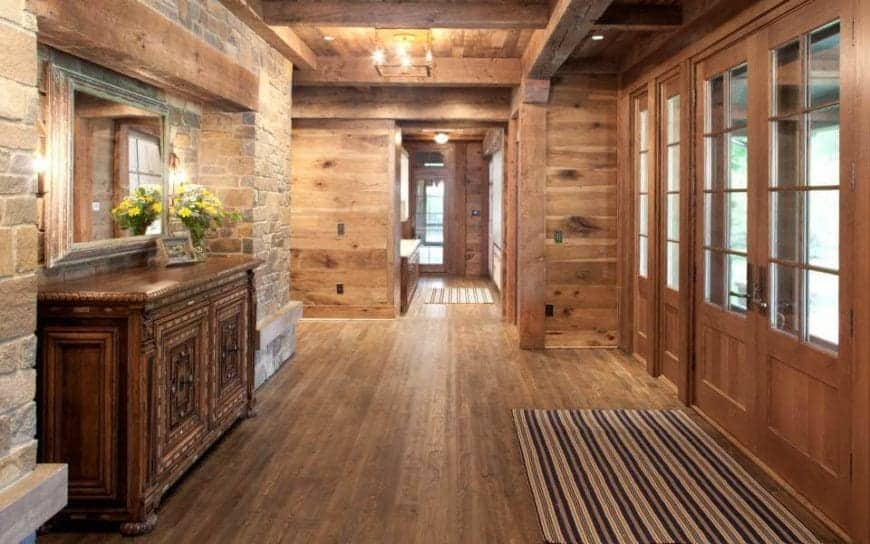 This charming foyer has set of double doors with a wooden finish and framing to its glass panels that bring in an abundance of natural lights to the hardwood flooring, wooden ceiling with exposed beams and the red brick wall across from the entrance.