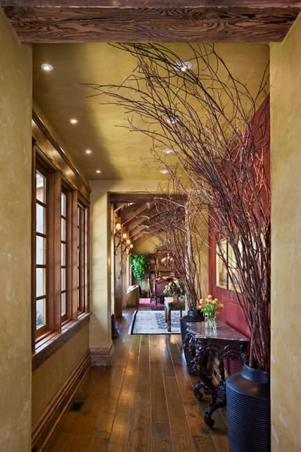 This hallway-like foyer has a beige ceiling filled with recessed lights. This blends with the beige walls that are dominated by a row of windows that cast natural lights to the intricate black console table on the opposite wall that has a red hue.