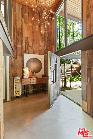 This is a charming Rustic-style foyer with a high ceiling adorned by a modern chandelier that gives off warm yellow lights. This complements the wooden walls and ceiling with a plank shiplap finish. These are also brightened by the large transom glass window.