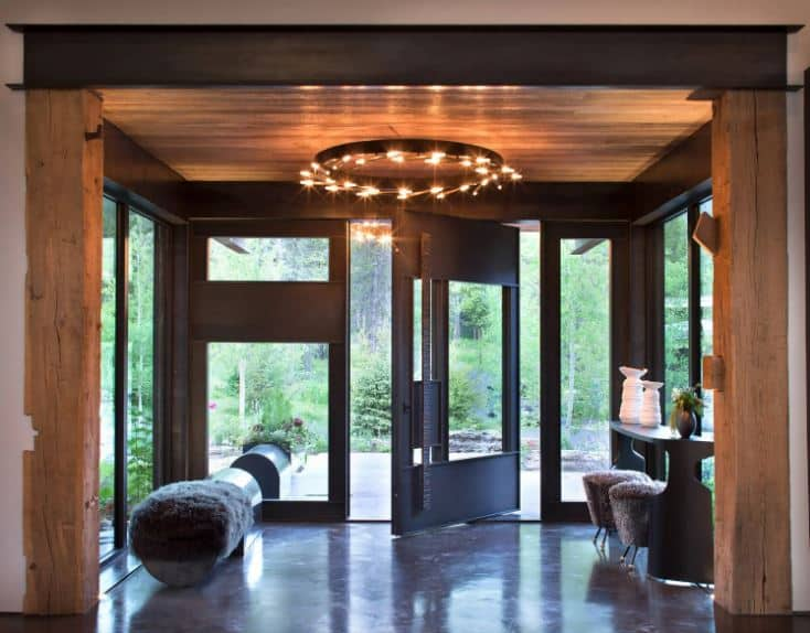 This bright foyer that is bathed in natural lights is augmented by the warmth of the yellow lights coming from the circular decorative chandelier above. This complements the wooden ceiling that is then contrasted by the dark modern frames of the glass walls and glass door that swivels to open.