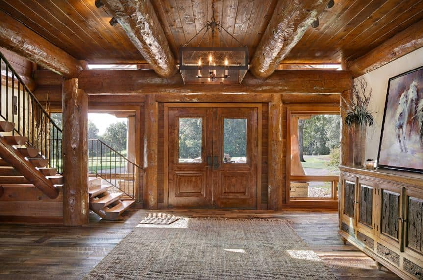 This Rustic-style foyer is dominated by a brown wooden tone that starts from the double doors with glass panels on them. This matches with the wooden ceiling with a couple of exposed thick log beams matching with the support column beside the wooden staircase.