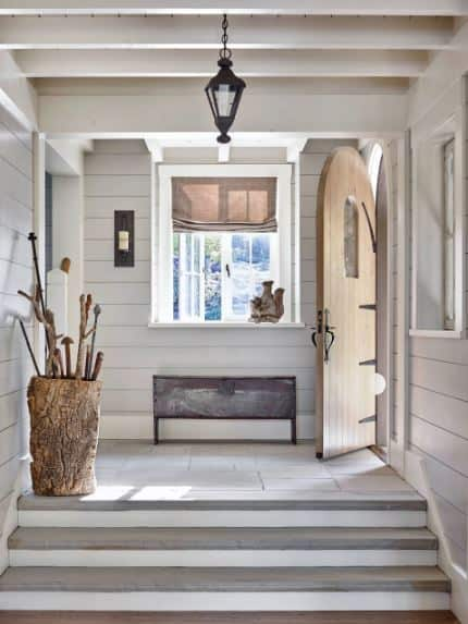 The brightness of this Rustic-style foyer is due to the natural lights coming from the window and opened door that brightens up the light gray shiplap walls and the white wooden ceiling with several exposed wooden beams contrasted by a black wrought iron pendant light.