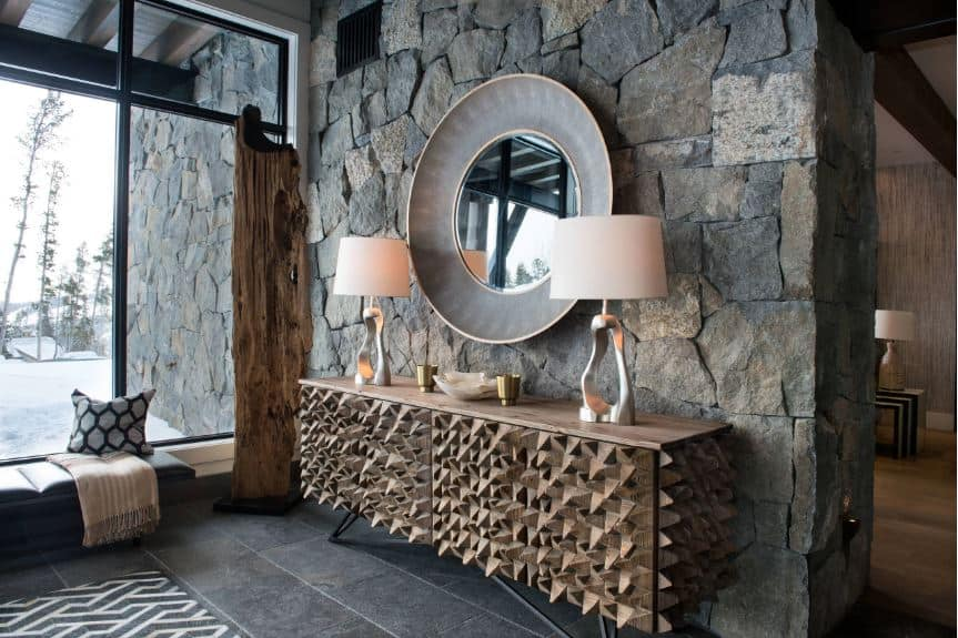 This bright foyer has an abundance of natural lights coming in from the large glass wall that lightens up the gray stone flooring and the textured stone wall adjacent to the glass wall adorned with a decorative console table and a large circular mirror above it.