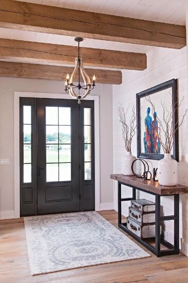 The black wooden door stands out against its glass panels and its matching side lights. This makes the white patterned area rug lighter. Beside this is a simple wood top console table with black iron legs. This is topped with a wall-mounted framed artwork.