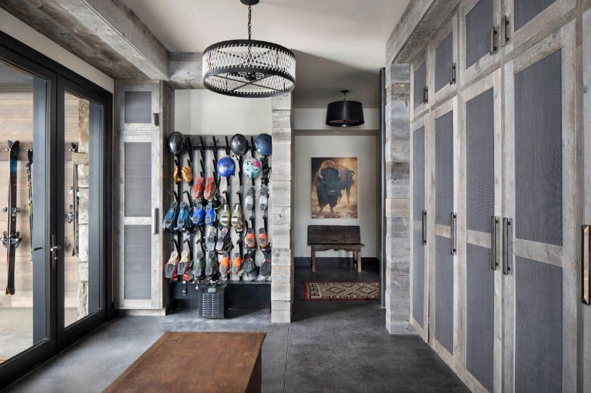 The glass doors with black frames lead to this foyer with a wonderful shoe and hat rack on the left. There is also a sitting area at the middle of the gray concrete flooring with a wooden bench facing a large built-in cabinet with screened wooden doors.