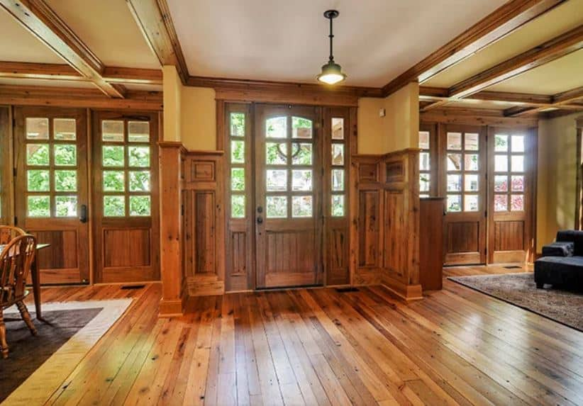 This simple Rustic-style foyer is dominated by the wooden tones of the plank hardwood flooring that extends to the wainscoting of the walls on either side of the side lights that matches with the wooden main door with glass panels. This connects with the wooden molding of the white ceiling.