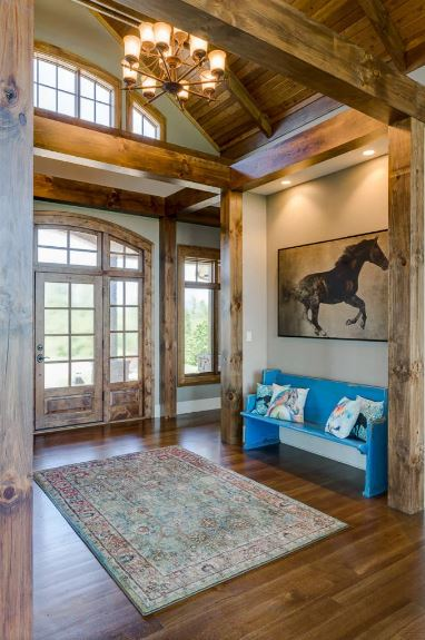 The main door is dominated by glass panels that match with its side lights and the arched transom window above. This brings in ample sunlight to the hardwood flooring and white walls augmented by the yellow recessed lights over the painting of a horse above the blue bench.