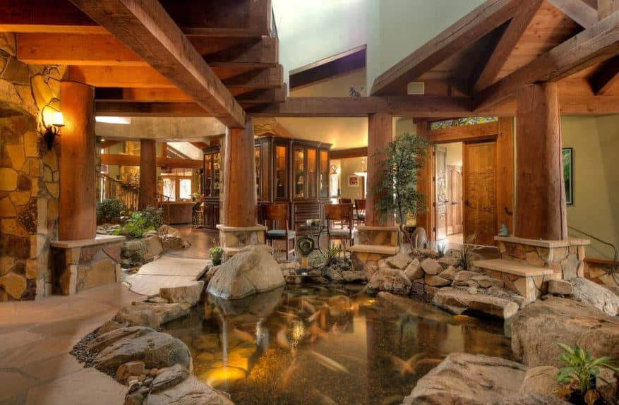 This amazing Rustic foyer has a zen aura to its koi pond right in the middle of the stone flooring. It is surrounded by thick wooden pillars connected to the wooden beams of the wooden ceiling matching with the beams framing the wooden main doors.