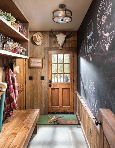 There is a decorative skull of a bull above the wooden main door hat leads to this hallway-like foyer. One of the walls of the hallway is made of black board that you can write on with chalk. This has a wooden wainscoting that matches with the wooden wall across it with a built-in bench and shelf above.