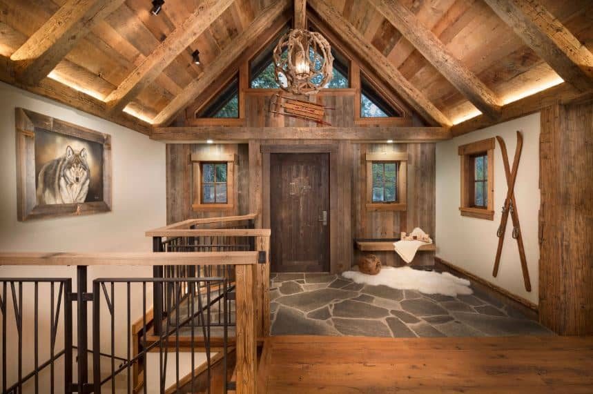The wooden cathedral ceiling of the foyer has a rustic-style pendant light hanging over the stone flooring. This complements the wooden wall that houses the main door that is flanked with windows and topped with a large transom window.