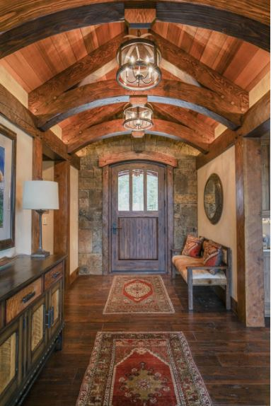 The wooden cove ceiling is adorned with exposed wooden beams that support small lantern-like flush mount lights. This complements the beige walls adorned with a large circular mirror mounted above the wooden cushioned bench on the side of the wooden main door.