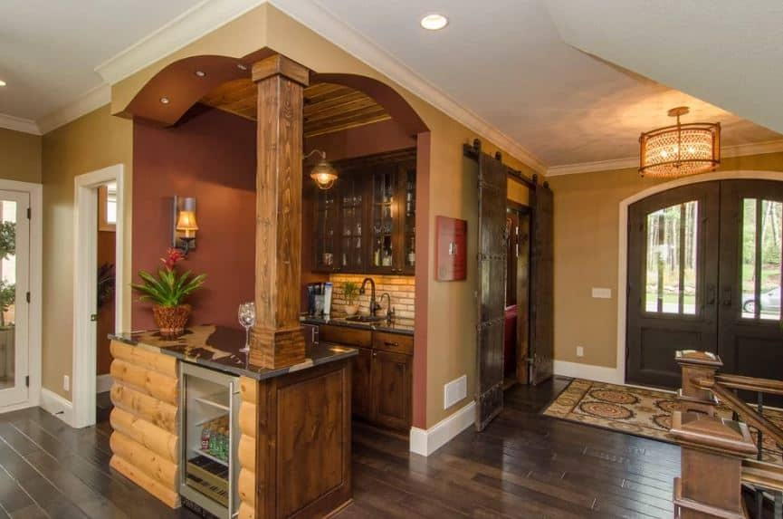 The double doors of this foyer has a dark brown hue and an arched design with glass panels on it. Upon entry, you area welcomed by the colorful patterned area rug placed on top of the dark hardwood flooring matching with the wooden sliding doors on the side.