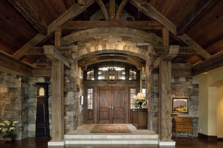 This Rustic foyer is slightly raised higher than the rest of the house with a white marble flooring. This makes the dark wooden tones of the main double doors and console table stand out. They work well with the textured stone walls as well as the lantern pendant light.