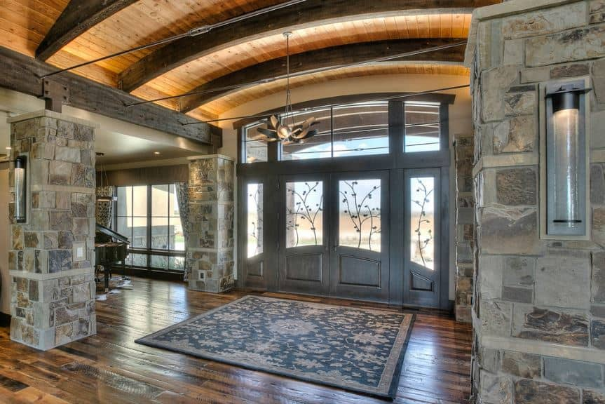 The glass panels of the gray wooden double door is adorned with depictions of branches and vines for a unique look on the main door. This is matched with the patterns of the colorful area rug placed on top of the hardwood flooring.