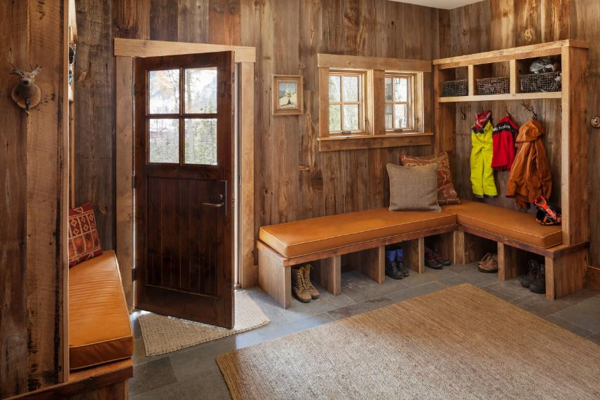 The wooden L-shaped cushioned bench is attached to a mudroom in this Rustic-style foyer with wooden walls. These wooden walls are complemented by the gray stone flooring that is mostly covered by a woven area rug.