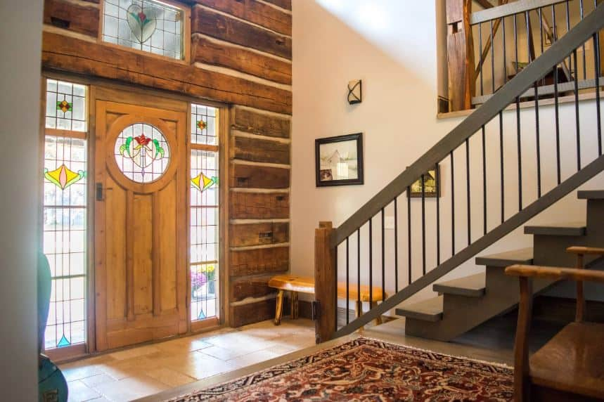 The main door, its side lights and transom window are all adorned with frosted glass and stained glass that brings in a dash of color to the wooden wall that houses the main door. This foyer leads to the gray staircase on its left beside the colorful patterned area rug.