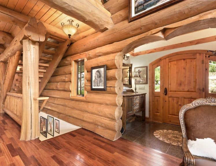 The small Rustic-style foyer of this log cabin has a charming wooden main door with an arched finish together with its side lights. This is complemented by a dark brown flooring adorned with a circular pattern in the middle that looks like a compass.