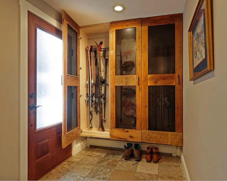 The simple and homey foyer has a small mudroom on the side of the main door that has screened cabinet doors for storage of winter sports equipment like skis and snowboards. Underneath it is a space for the shoes on the beige marble flooring.