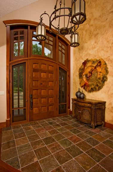 The highlight of this Rustic-style foyer is the majestic arched main door that is surrounded by glass panels of the side lights and large transom window that maximizes the vertical space. Adjacent to this is a yellow wall with a decorative wall clock shaped like a flower.