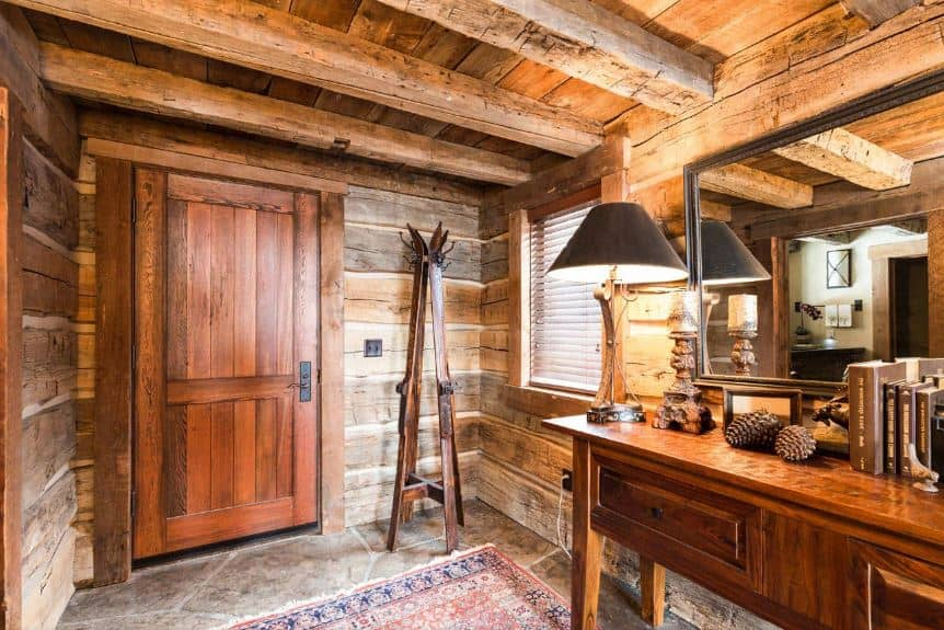 The wooden ceiling of this foyer has exposed wooden beams that matches with the wooden planks that adorn the walls. These are then complemented by the sleek redwood materials of the wooden main door with a standing coat rack on the side made of repurposed skis.