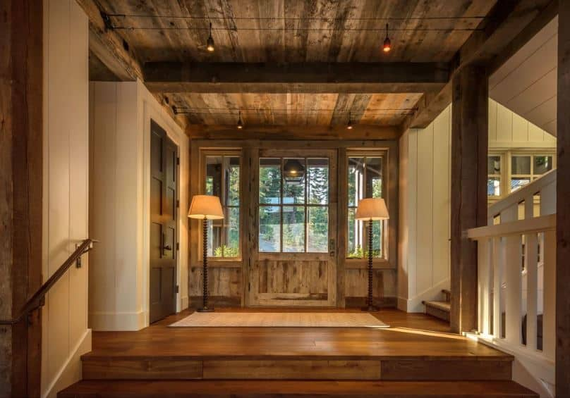 The wooden main door is mostly dominated by glass panels on it that matches with the side lighting. These side lighting are adorned with a couple of standing lamps that casts off warm yellow lights that complement the wooden elements that dominated the foyer.