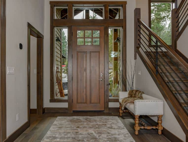 The lovely wooden bench on the side of this foyer is upholstered with white leather and studs matching the white walls by contrasting the dark hardwood flooring and the wooden main door that has side lights and a transom window.