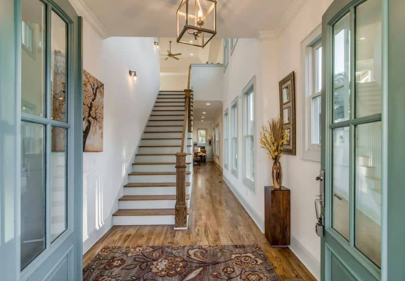 The chic light green double doors opens up to this simple Rustic-style foyer topped with a lantern pendant light that illuminates the white ceiling. This blends with the white walls that are contrasted by the hardwood flooring and its small console table.