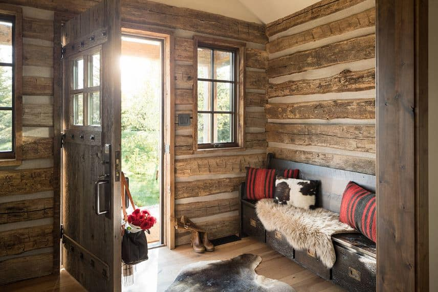 The white walls of this small Rustic-style foyer is filled with strips of log. These planks matches well with the wooden main door that has metal studs on it. It also complements the hardwood flooring and the dark wooden bench that has drawers underneath.
