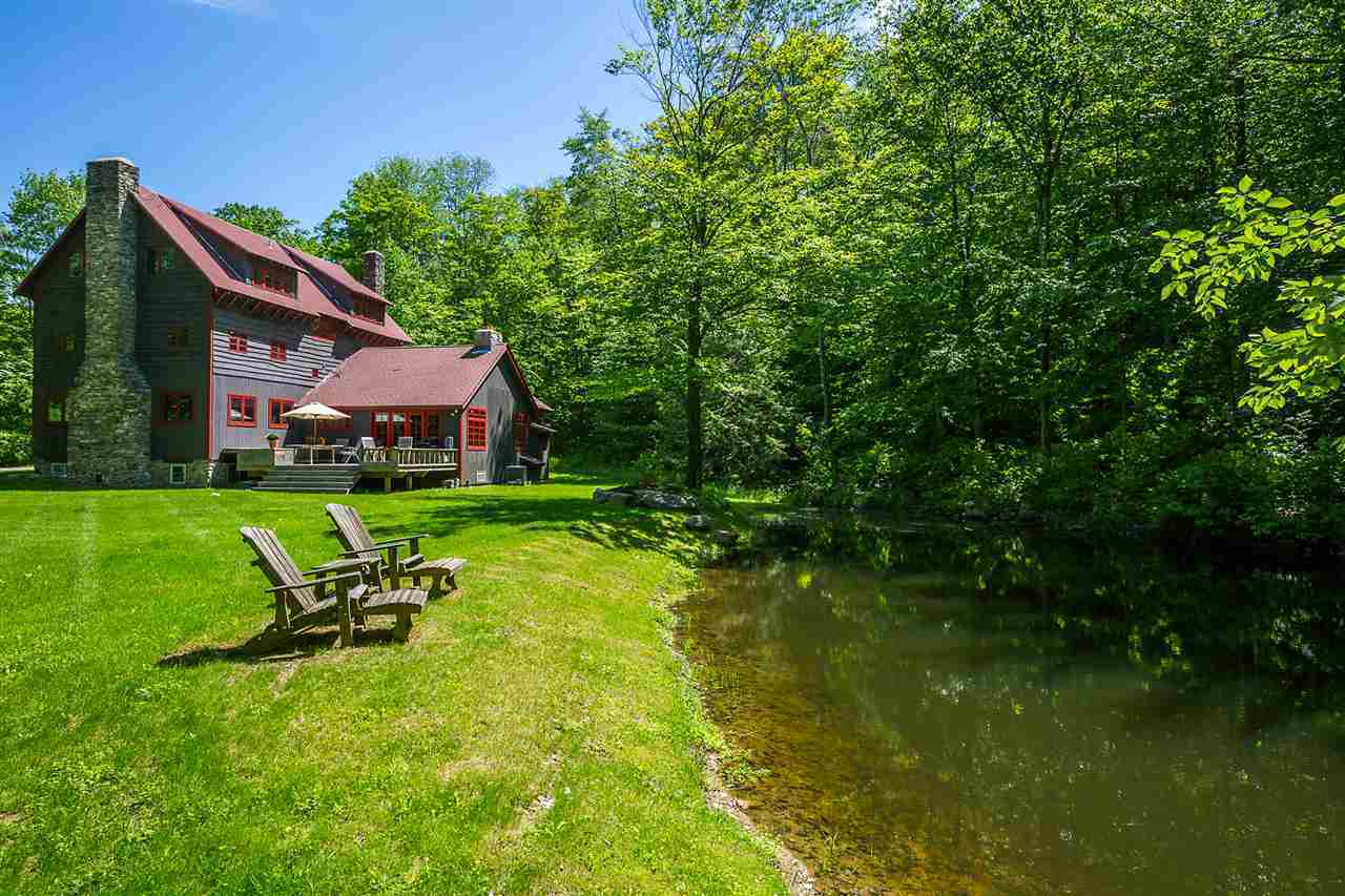 This charming home sits beside a quaint riverside scenery with tall trees and well-manicured grass. A couple of wooden lawn chairs are placed by the scenery as well as an outdoor patio behind the home for those who want to sit and relax gazing at this beautiful Rustic-style landscape.