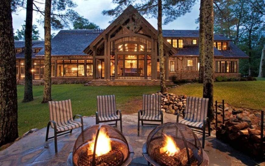 This beautiful backyard has several tall trees with carpets of grass in between. This leads to a small area with a circular floor of stone and two firepits paired with four sling chairs with metal frames. This is given a nice background of the brilliantly lit home.