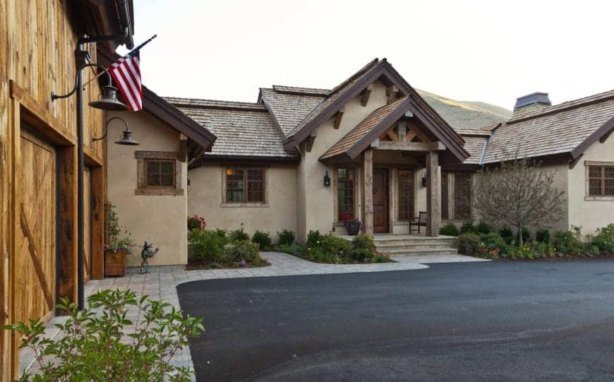 This is the front of the home that has a black asphalt driveway leading to wooden barn-like garage doors. Adjacent to this is the entryway that has a few stone steps leading to the wooden main door. This whole area is accented with the shrubs and flowering plants that stand out against the beige exterior walls.