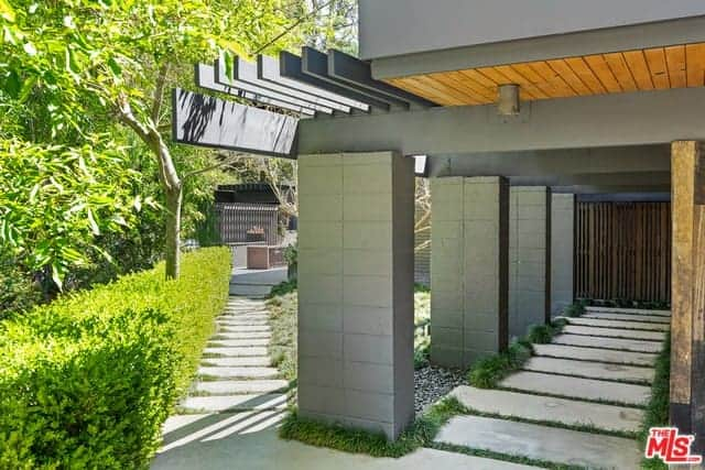 This is a view of the side of the home that has thick gray stone columns that support the gray beams of the trellises above. These columns stand at a fork in the middle of two concrete walkways where one leads to the side and one leads to the back bordered with shrubs.
