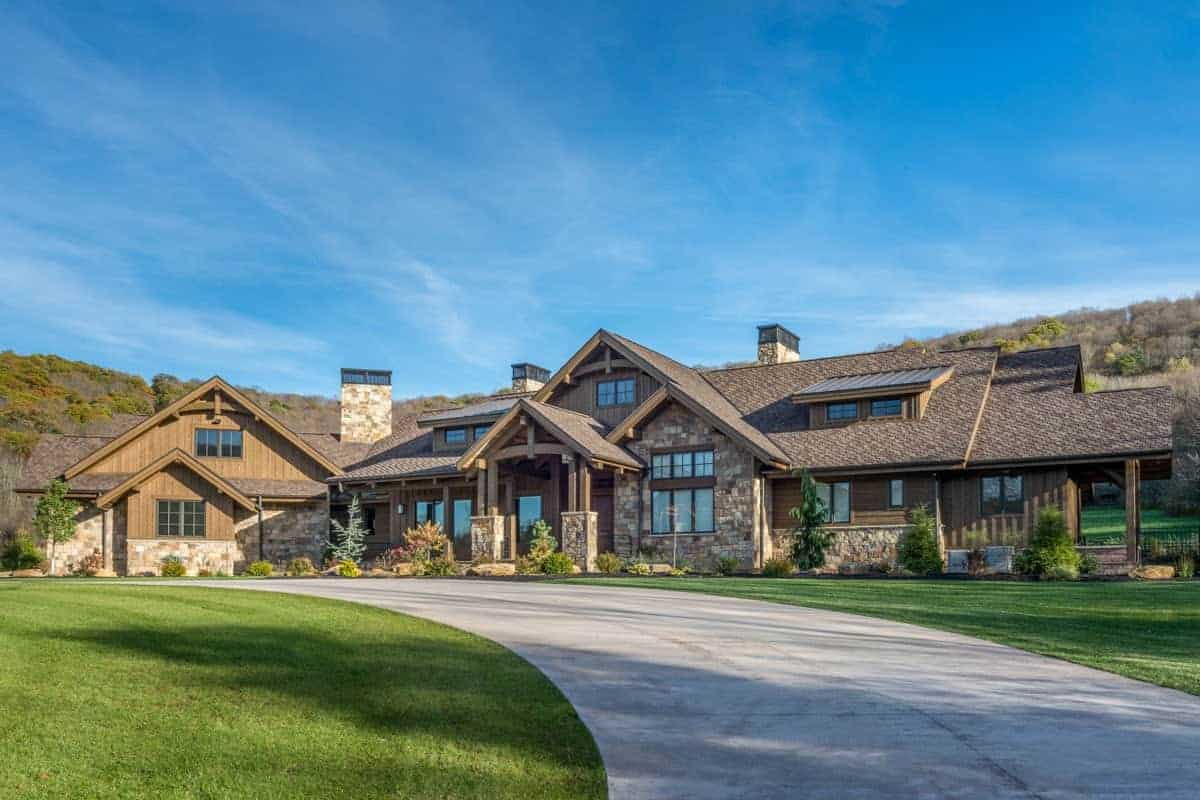 This Rustic-style landscaping accents the beauty of the home that is dominated by wooden and stone materials of the exteriors. There is a winding and wide concrete walkway and driveway that cuts through a wide expanse of well-manicured grass lawns leading to the house that is lined on the sides with shrubs.