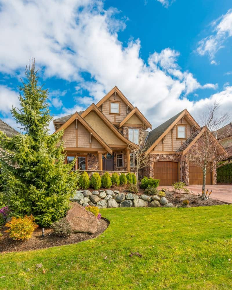 The charming home has two wooden garage doors and a wide terracotta driveway leading up to it. This drive is adorned with an amazing landscape on the left side at the front lawn. The highlight is a handsome pine tree surrounded by colorful bushes and spotlights to emphasize it more at night.