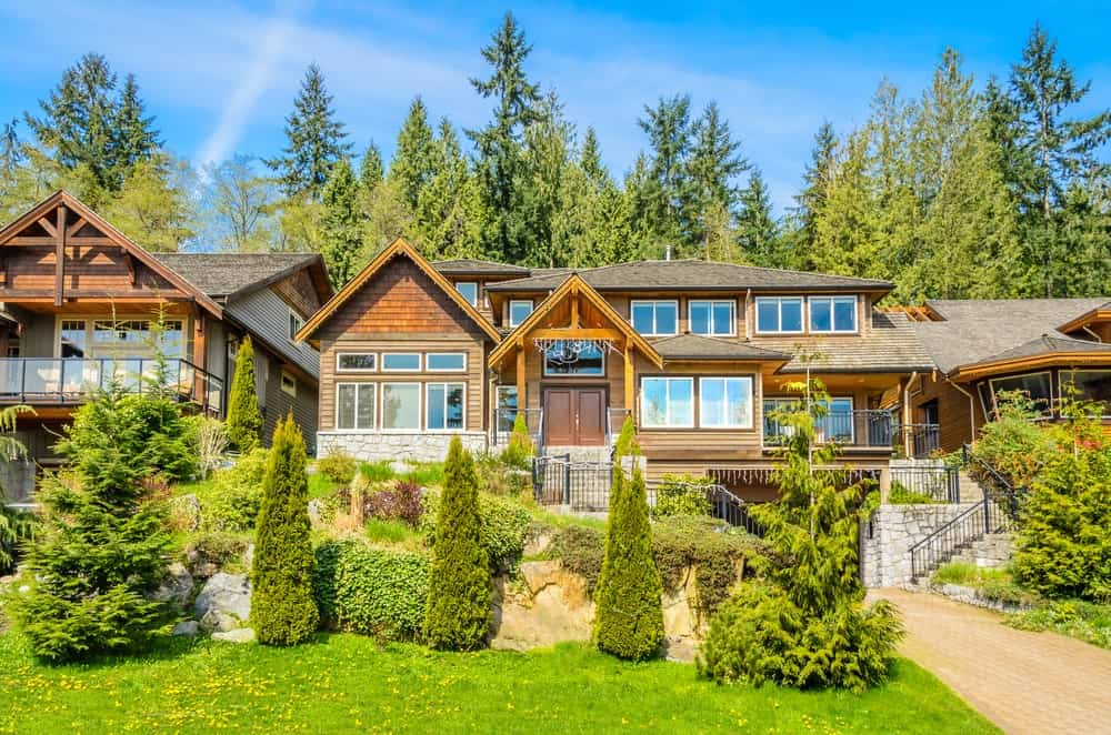 This view features the beautiful Rustic-style landscaping that sets a nice foreground for the elevated home. This is reached through stone steps with metal railings. This is decorated with various shrubs and medium-sized trees to make the short walk up to the entrance a delightful experience.