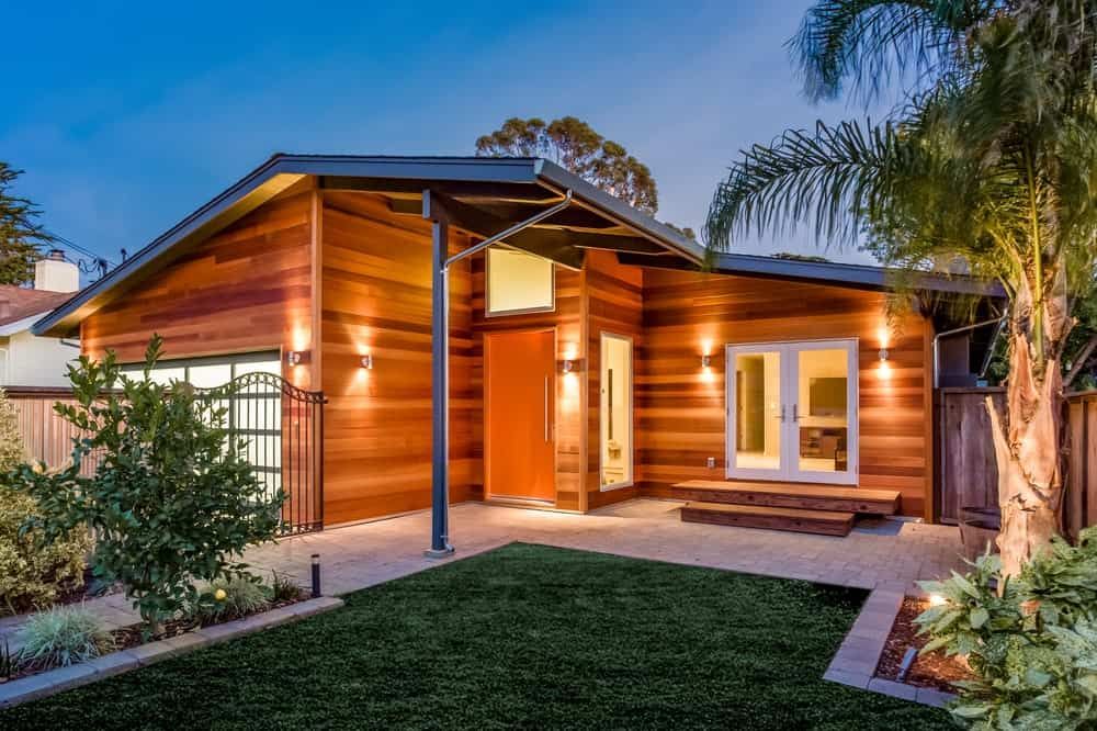 The wooden exterior walls of this home is augmented by the wall-mounted lamps that cast warm yellow lights. This same hue brightens the tropical tree by the side of the well-manicured grass lawn leading to concrete walkways and then to wooden steps to the house.