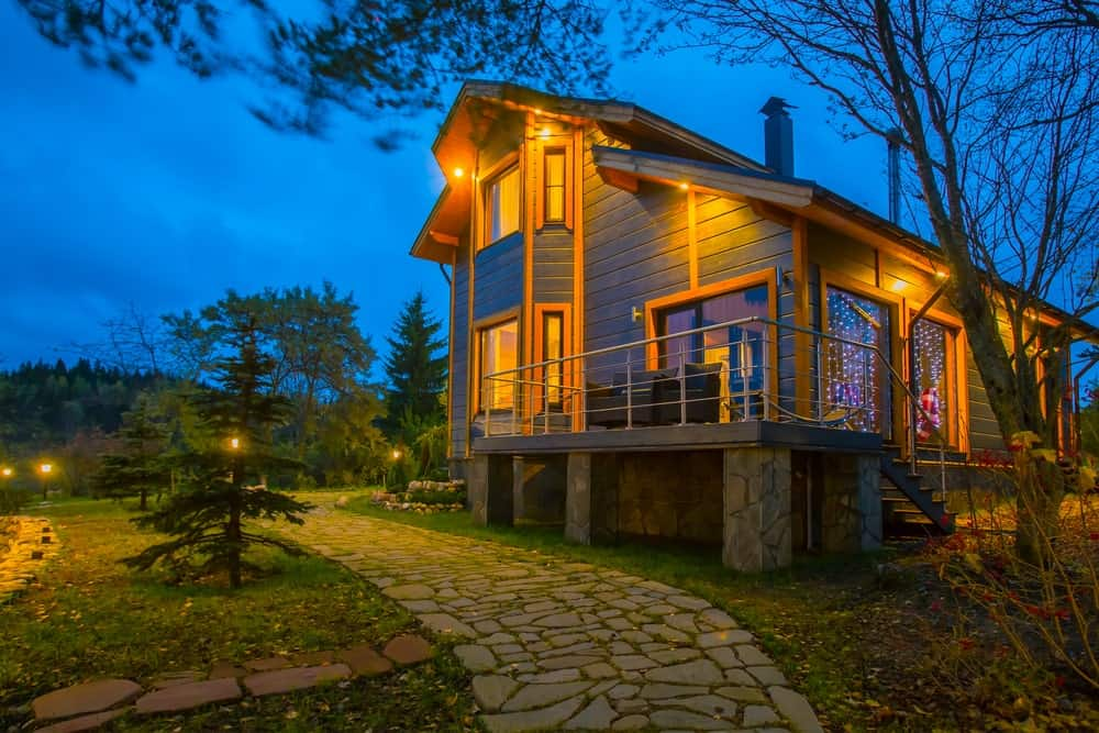 This bright and warm home is surrounded by well-manicured grass that has embedded pieces of stone building a walkway with a unique look. This walkway is lit with the same yellow lights of the house through small posts.