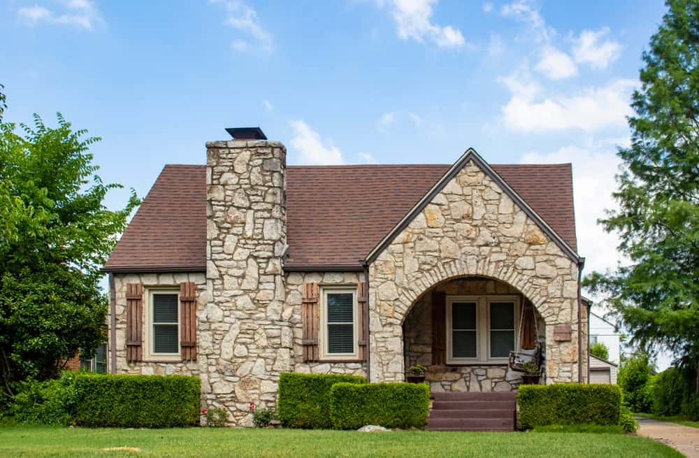 This charming home is augmented by the simple Rustic-style landscaping of green grass that is cut short and the dense shrubs that line the base of the stone exterior walls. They also flank the wooden stairs leading to an arched entryway.