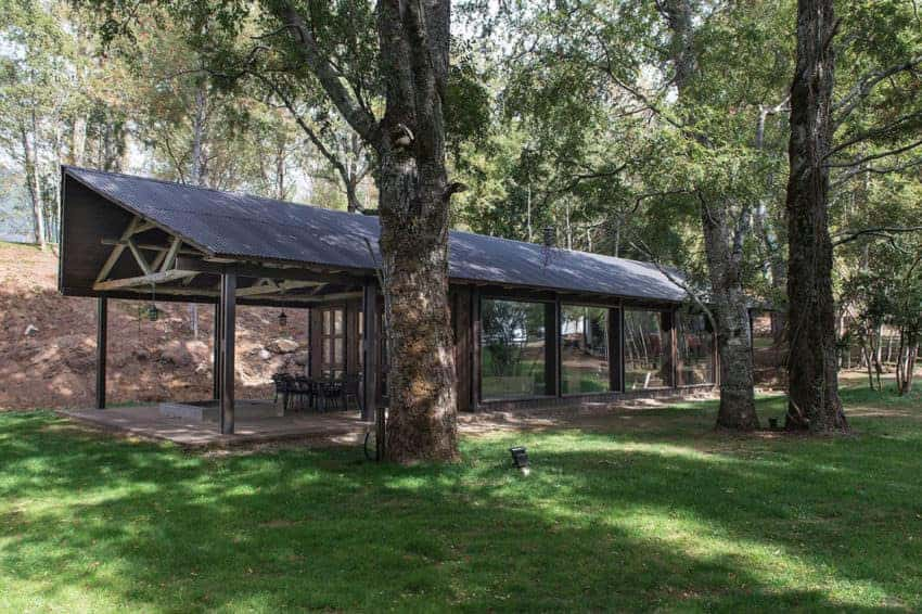 This is a beautiful home filled with glass walls that make it seem like those inside are a part of the surrounding dense forest of tall trees and well manicure lawns of grass. There are embedded spot lights at foot of trees to illuminate the surrounding foliage at night.