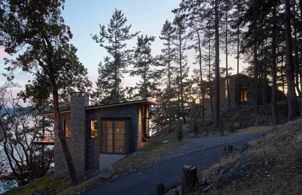 This charming home is built on an incline by the side of a hill. The Rustic-style landscaping used here is specifically designed to blend with the existing natural scenery. There is also a graveled walkway diverging from the main road towards the entryway of the home lined with small pines.