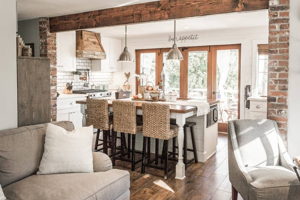 An open kitchen with white cabinets and a rustic vent hood fixed against the subway tile backsplash. There's a shiplap island in the middle that's accompanied by wicker counter chairs and chrome <a class=