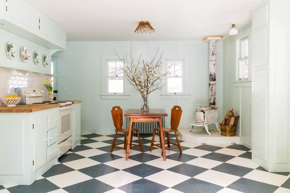 An eat-in kitchen designed with a glass flower vase and decorative plates mounted above the floating shelf. It has a freestanding fireplace and wooden dining set over checkered flooring lighted by a brass flush mount light.