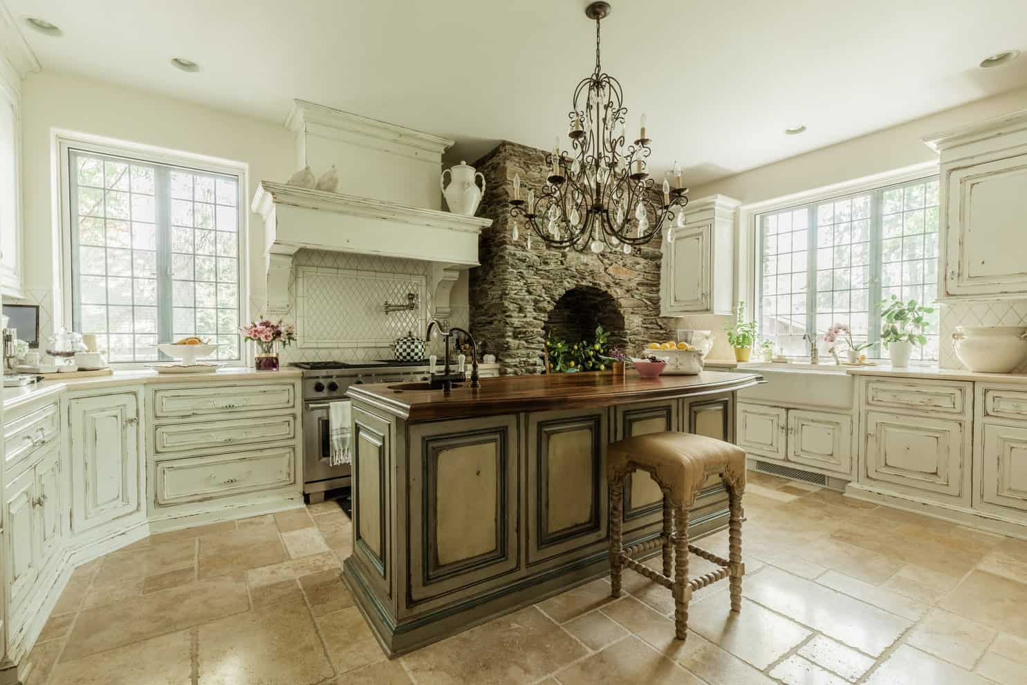 A grand candle chandelier hangs over the wooden top island paired with a cushioned stool on limestone flooring. It has stainless steel appliances and a farmhouse sink that blends in with the distressed white cabinets.