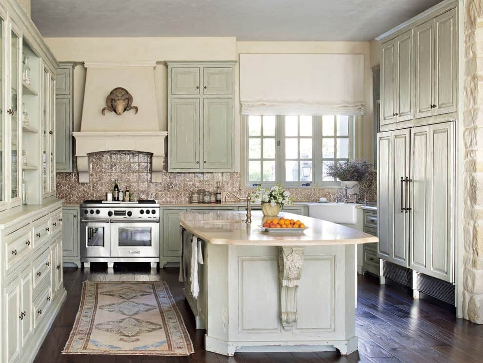 Shabby-chic style kitchen offers distressed cabinets and a matching island topped with a beige counter. It includes a classic bordered runner and a stainless steel range under a vent hood that's designed with an animal head decor.