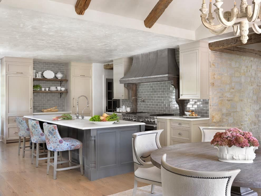 Gorgeous floral chairs sit at a gray breakfast island fitted with a sink and chrome fixtures. It is accompanied by white cabinetry and a rustic range hood fixed against the subway tile backsplash.