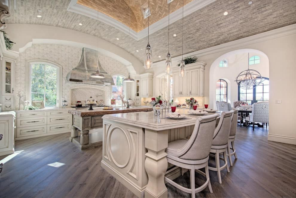 Deluxe kitchen showcases two island bars and white cabinetry that blends in with the walls. It has natural hardwood flooring and a barrel-vaulted ceiling clad in bricks.