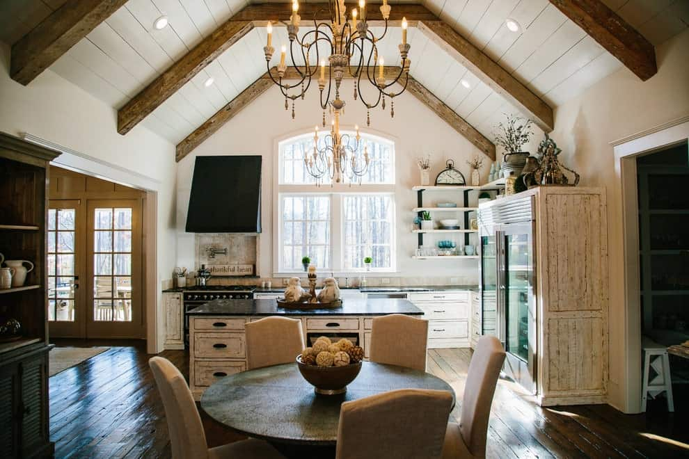 A dine-in kitchen with distressed white cabinets and island topped with black granite counters. It is illuminated by candle chandeliers and recessed lights mounted on the shiplap vaulted ceiling that's lined with rustic beams.
